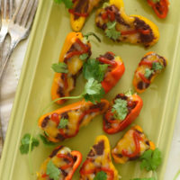 Black Bean Stuffed Mini Pepper Bites - A protein-packed snack, or fun party appetizer! Mini bell peppers stuffed with refried black beans and topped with cheese.   foxeslovelemons.com