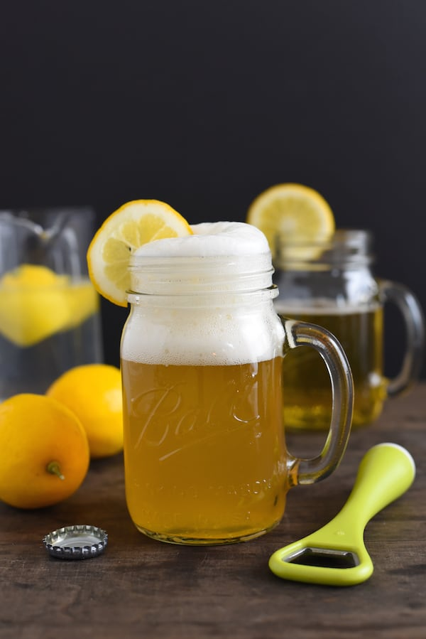 Wheat beer shandy in glass mug with lemons in background.