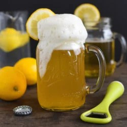 Lemon shandy in mason jar mug with bottle opener and lemons in background.