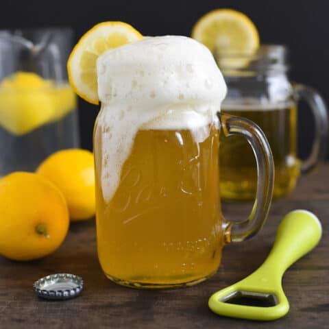 Lemon shandy in mason jar mug with bottle opener and lemons in background.
