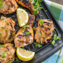 Grilled chicken pieces on black tray with lemon wedges and herbs.