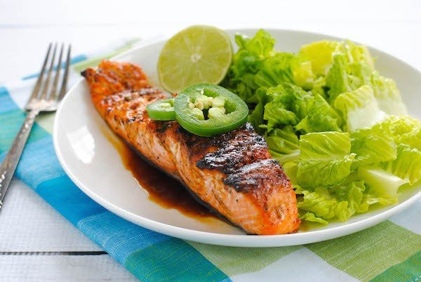 Grilled Salmon with Sweet Jalapeño Glaze - This will be your go-to weeknight meal this summer! Grilled salmon is brushed with a sweet and spicy glaze for a healthful and delicious meal.   foxeslovelemons.com
