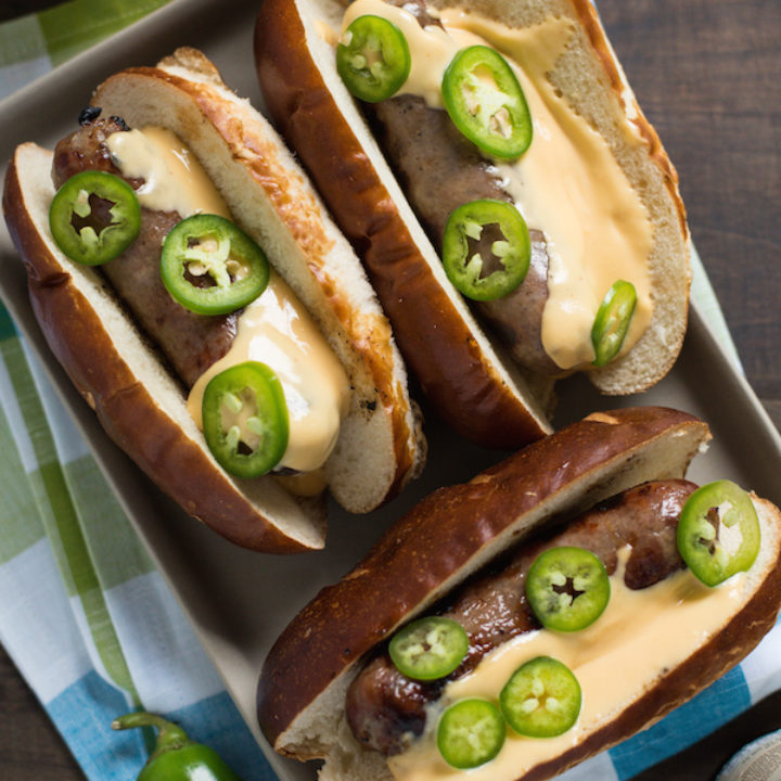 Beer Brats with Beer Queso - For the beer and grilling lovers in your life! Beer-flavored bratwurst topped with a sharp cheddar-beer queso. Serve with beer! | foxeslovelemons.com