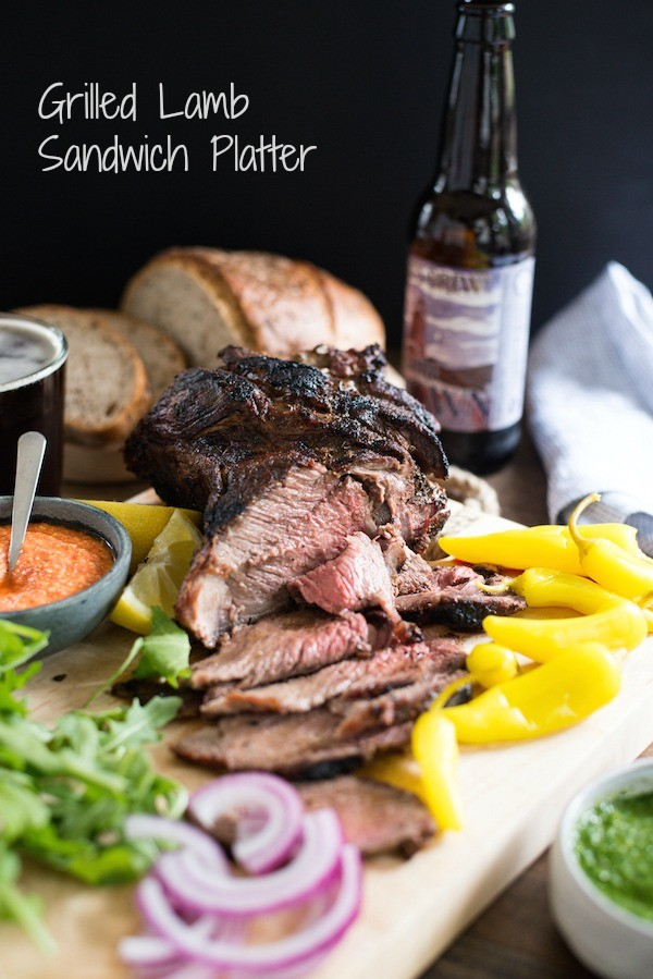 Grilled Lamb Sandwich Platter - Change up your grilling game with a boneless leg of lamb! It cooks in the same amount of time as a thick steak, and has a rich delicious flavor. Pile sandwich fixings, zesty feta spread, chimichurri and rye bread onto a big board, and dinner is served!   foxeslovelemons.com