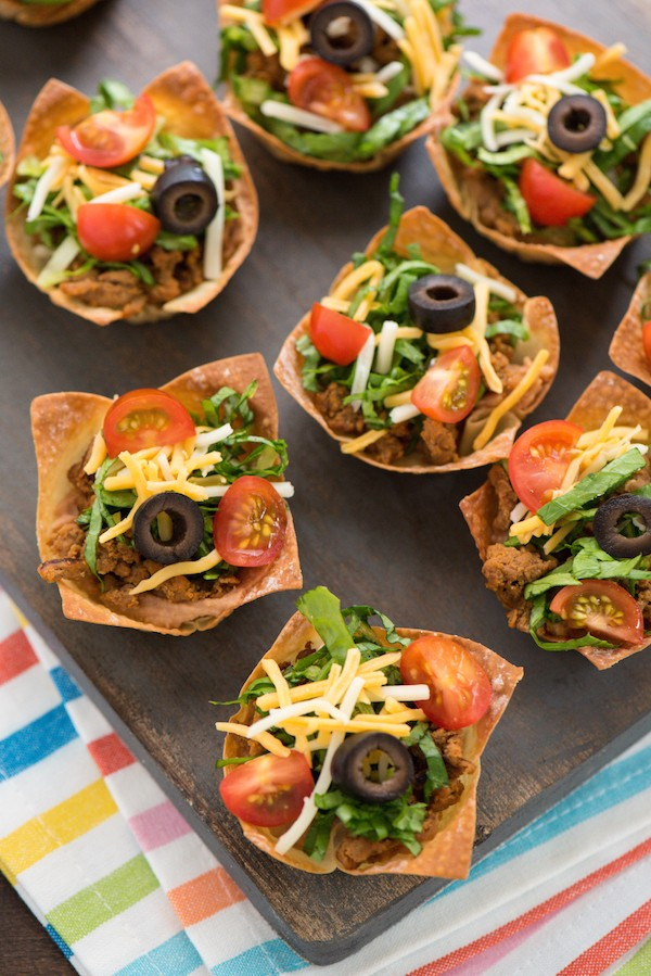 "Mini Turkey Taco Salads - An appetizer-sized version of the restaurant classic! Layers of beans, seasoned ground turkey, cheese, lettuce and tomato inside of wonton wrapper ""taco shell"" bowls! 