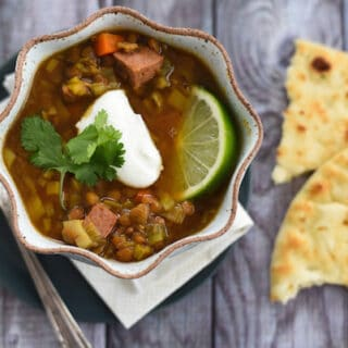 Lentil and sausage soup in rustic bowl with naan bread on side.