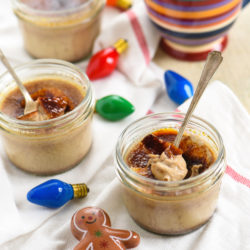 Small mason jars of creme brulee with christmas decorations.