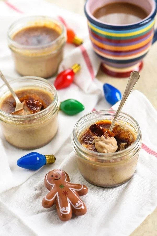 Small mason jars filled with torched ginger bread custard, with spoons in them. Christmas tree lightbulbs and a ceramic gingerbread person decorate the scene.
