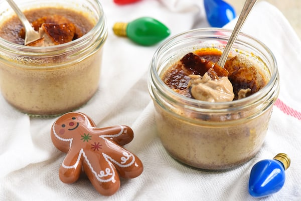 Small mason jars filled with holiday creme brulee, with christmas tree lightbulbs and a ceramic ginger bread person decorating the table.