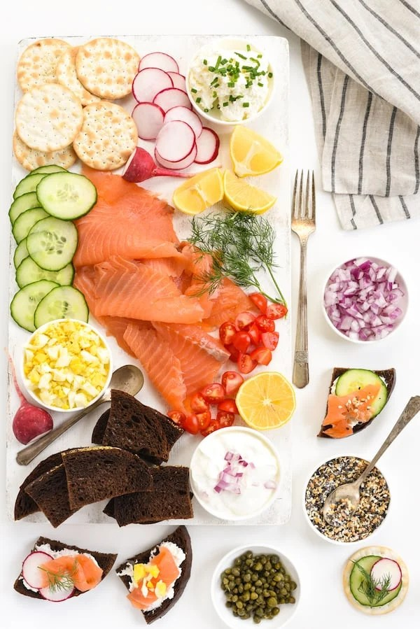 Overhead photo of platter with smoked salmon, bread, crackers, spreads and garnishes.