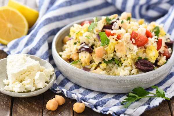 Closeup on bowl of fried rice with chicken, feta cheese, olives, tomatoes and chickpeas.