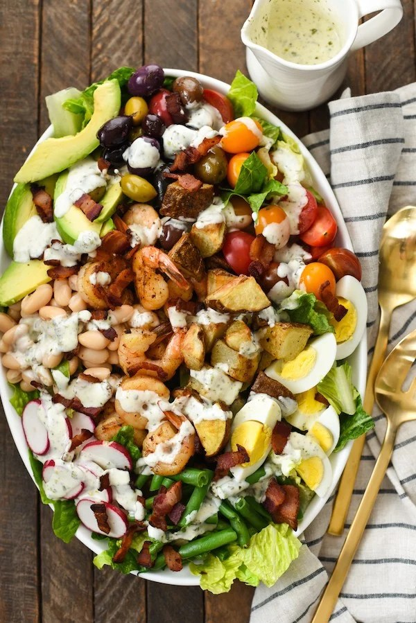 Mega Chopped Salad with Shrimp & Roasted Potatoes - Clean out your fridge and pantry for this salad that is a meal itself. Drizzle with homemade Pesto Ranch Dressing (recipe included).   foxeslovelemons.com