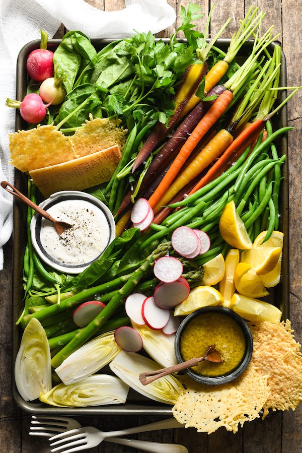 DIY Spring Salad Board - Assemble a bounty of spring produce on a platter, along with creamy Parmesan-Peppercorn Dressing, tangy Parmesan Vinaigrette, and crunchy Parmesan Fricos, and let your guests assemble their own salad with this fun party idea! | foxeslovelemons.com
