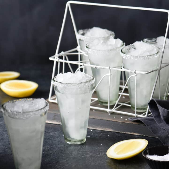 Set of small, tall glasses, filled with ice and a clear beverage, with cut lemons and salt nearby.