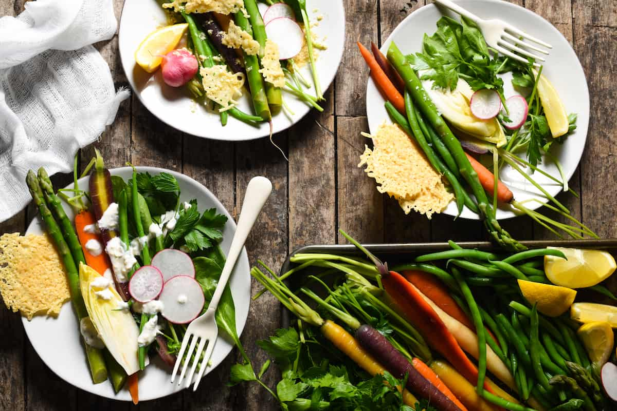 DIY Spring Salad Board - Assemble a bounty of spring produce on a platter, along with creamy Parmesan-Peppercorn Dressing, tangy Parmesan Vinaigrette, and crunchy Parmesan Fricos, and let your guests assemble their own salad with this fun party idea!   foxeslovelemons.com