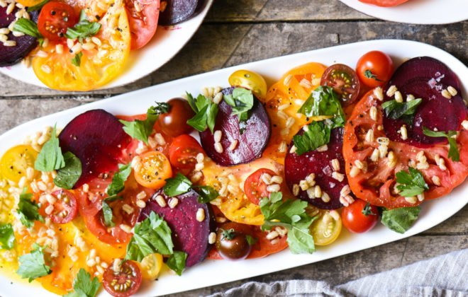Horizontal overhead photo of oblong platter of tomato and beet salad.