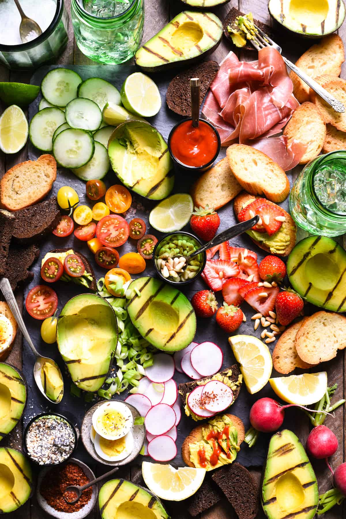 Grilled Avocado Crostini Board - A fun party idea! Pile a bunch of fresh toppings onto a big platter, and let your guests assemble their own grilled avocado crostini! | foxeslovelemons.com