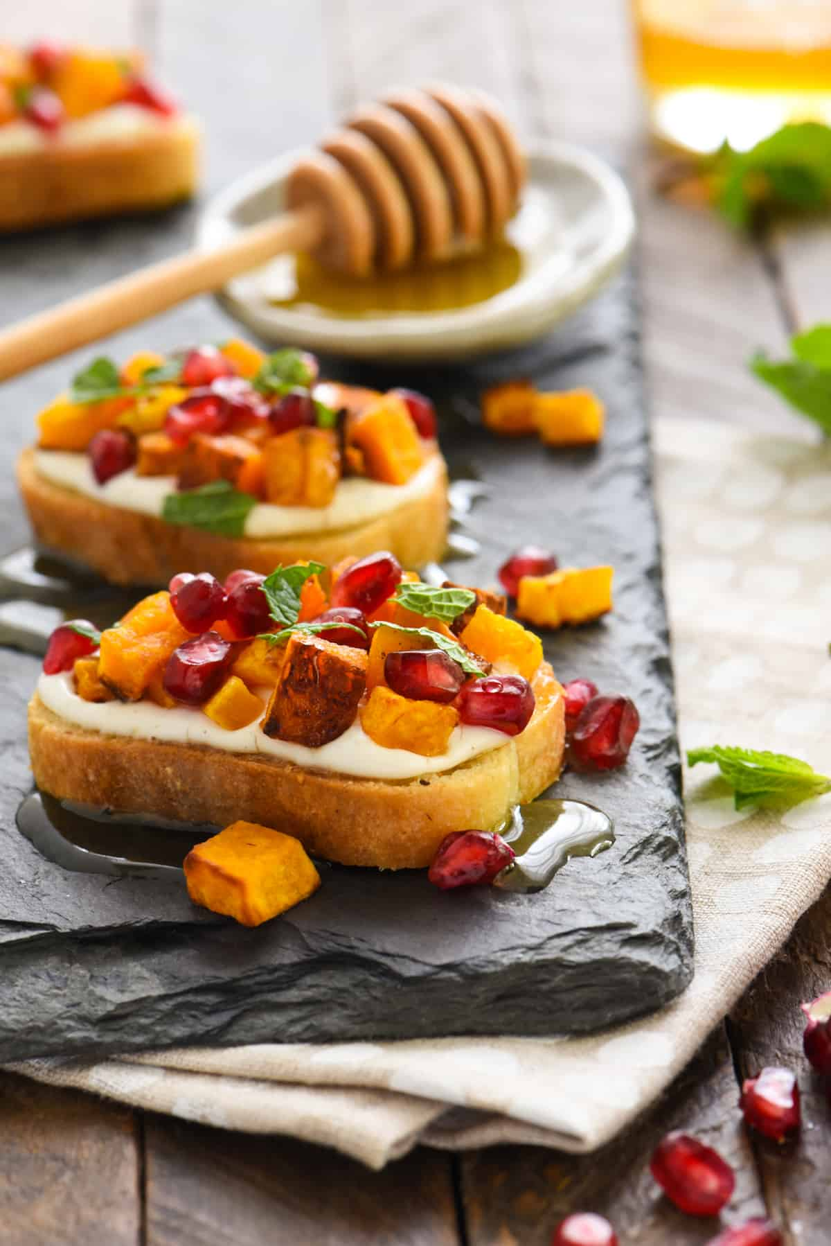 Crostini topped with white sauce, butternut squash and pomegranate seeds, on slate platter.