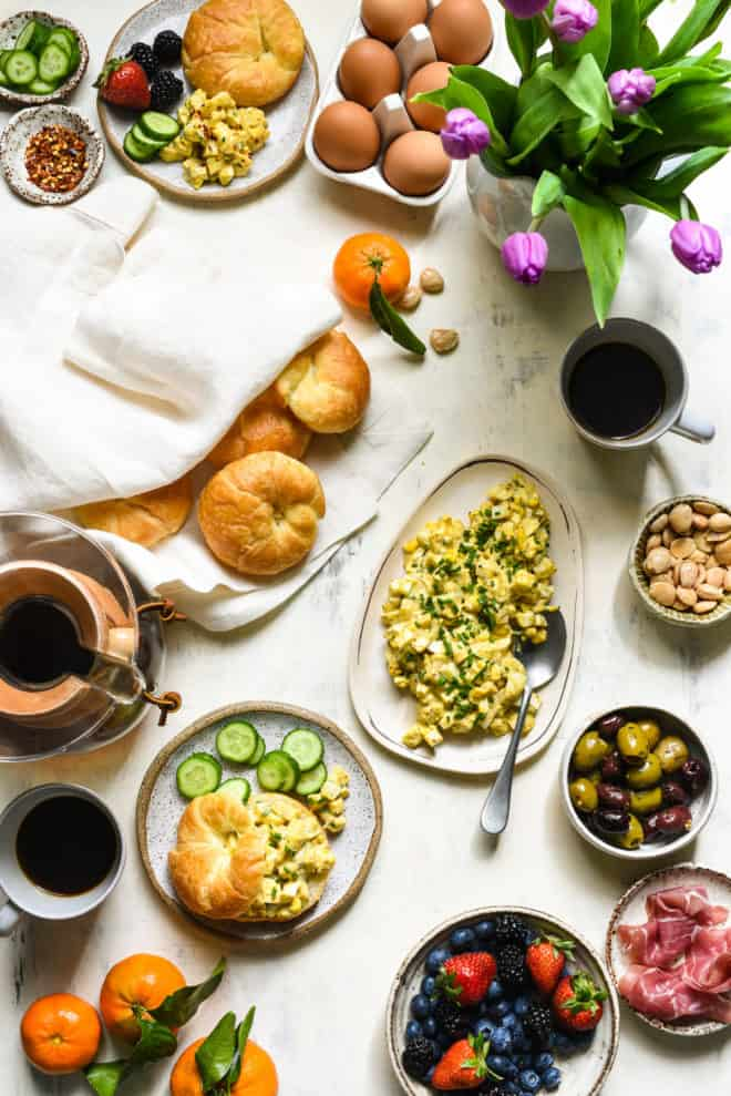 Light tabletop covered with croissants, flowers, fruit, egg salad and coffee.