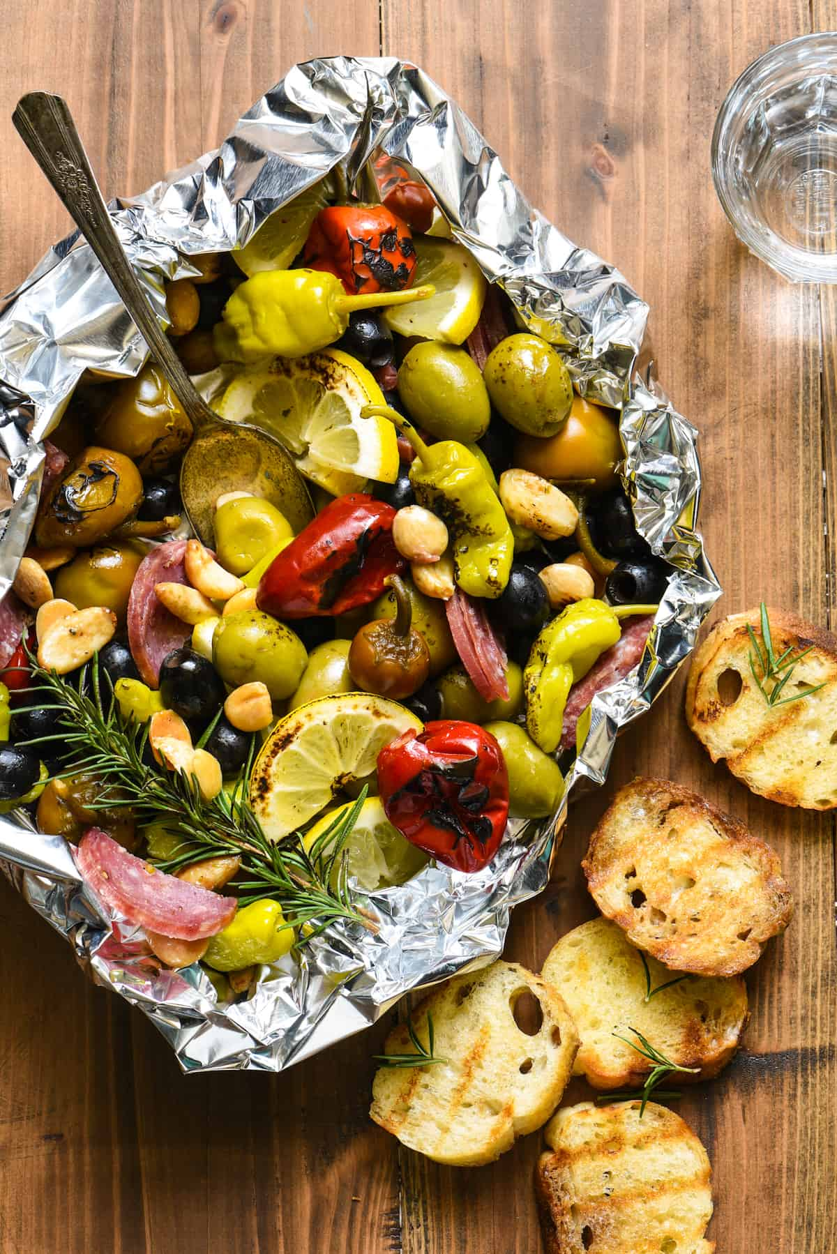 Fill a foil packet with olives, peppers, nuts and salami and throw it on the grill! This Grill-Roasted Antipasto will be the easiest summer appetizer you'll ever make! | foxeslovelemons.com