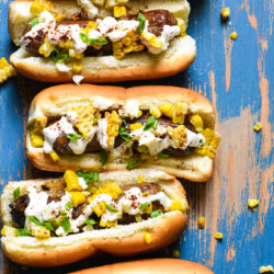 Inspired by elote, these Mexican Street Corn Brats are ideal for a summer celebration or easy weeknight meal! Spicy sausages are topped with fresh sweet corn, creamy lime sauce and tangy cheese.| foxeslovelemons.com