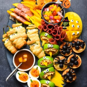 Large platter of spooky halloween food on dark background.