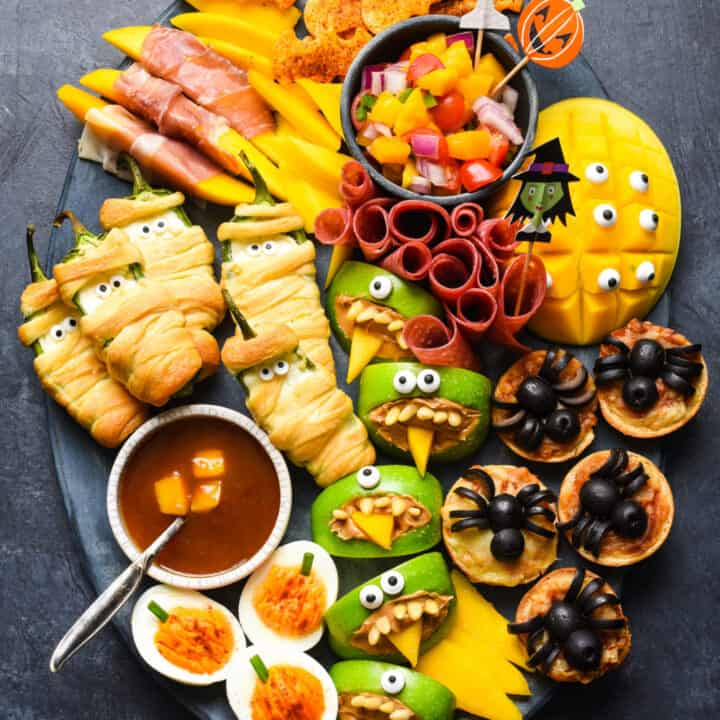Large platter of spooky halloween food on dark background.