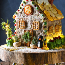 A savory gingerbread house on a wooden stand, with holiday lights decorating the scene.