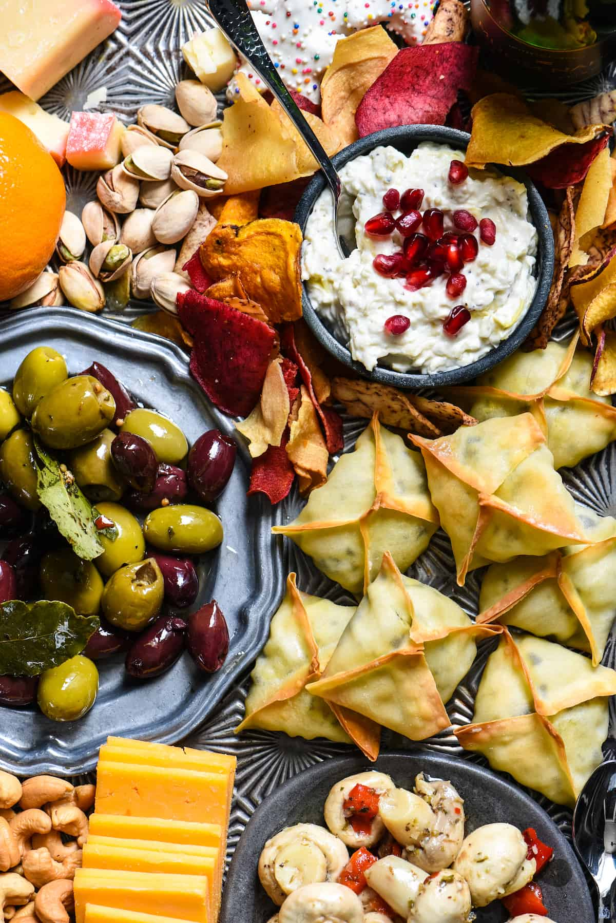 Closeup photo of platter of New Year's Eve finger foods, focusing on wontons, olives and creamy dip.