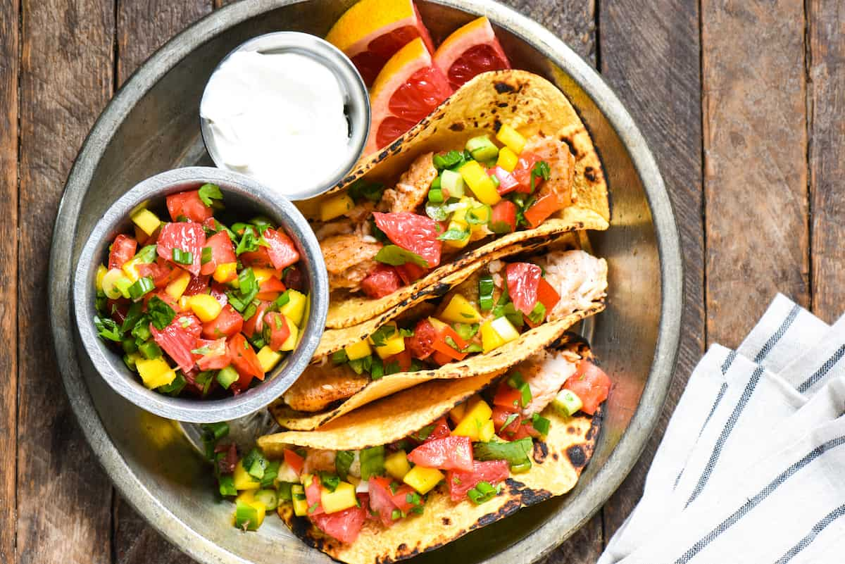 Tequila Fish Tacos with Grapefruit Salsa + 11 Grapefruit Recipes to Brighten Your Winter - Bring some happy flavor to a cold day with an appetizer, cocktail, breakfast, salad, lunch or dinner celebrating juicy, sweet grapefruit! | foxeslovelemons.com
