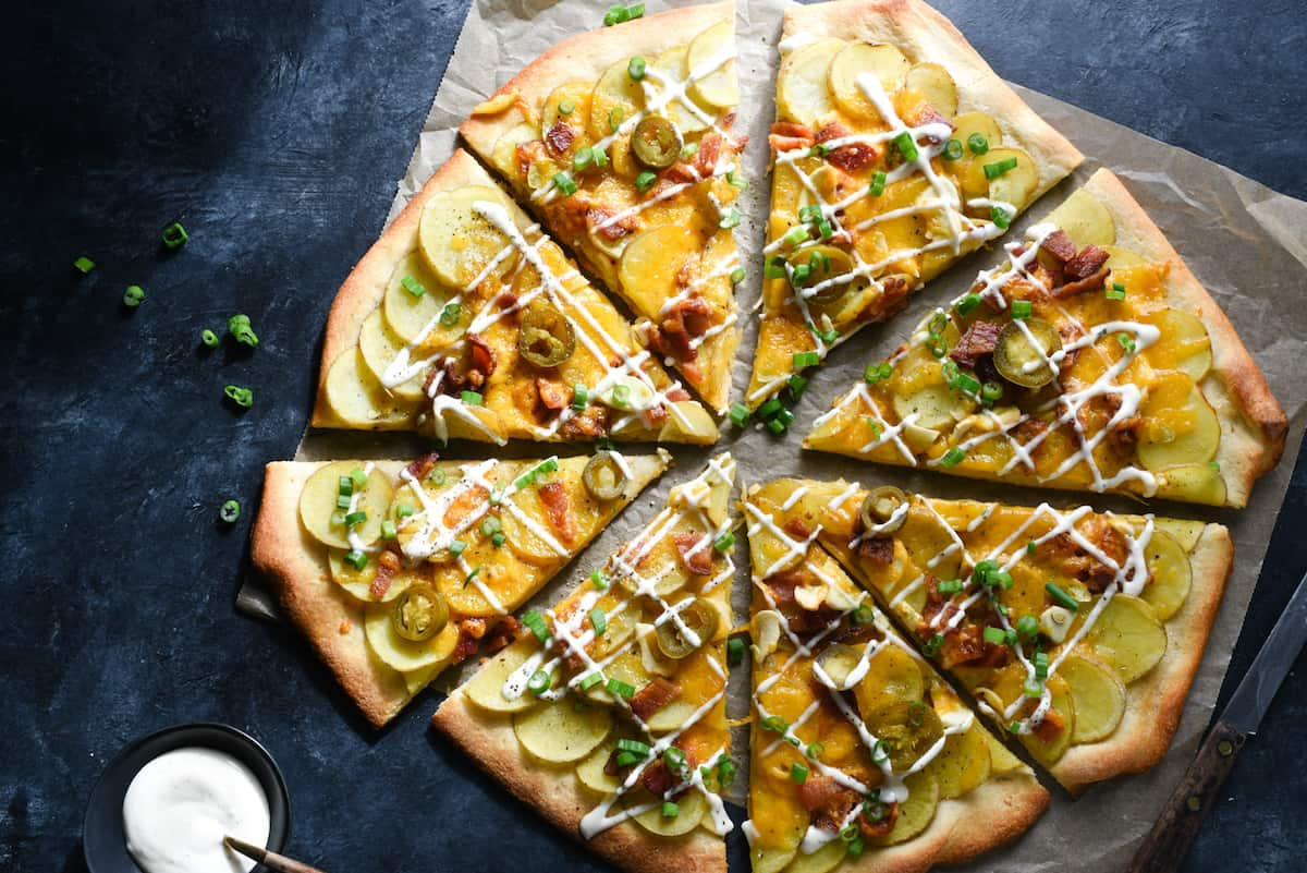 This Loaded Baked Potato Pizza is packed with all of the flavors you love from stuffed baked potatoes, like bacon, cheese and ranch dressing! This recipe comes together with ingredients easy to find at any grocery store. | foxeslovelemons.com