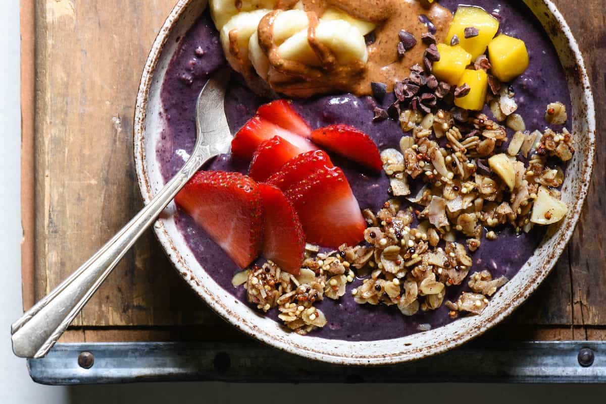Get your day started with the powerful superfoods in these Açaí Bowls with Maple Quinoa Granola! Berry and banana smoothie bowls are topped with easy homemade granola, fresh fruit and almond butter. Naturally gluten free and vegan. | foxeslovelemons.com
