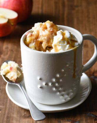 Textured ceramic mug filled with apple mug cake, topped with whipped cream and caramel.