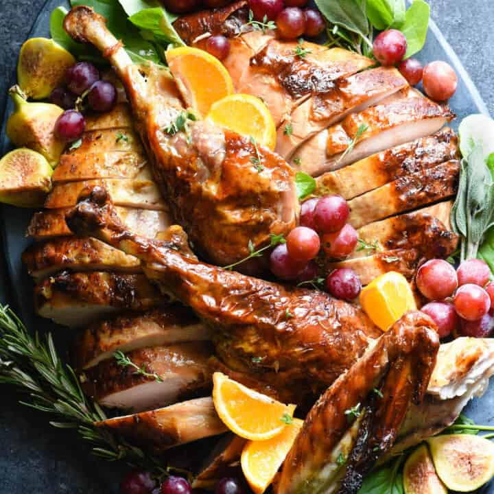 Large slate blue ceramic platter filled with a cut up roasted turkey, garnished with grapes, orange slices and herbs.