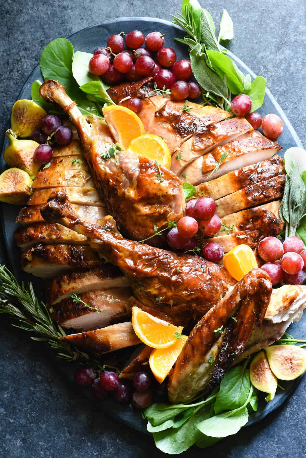 Large platter filled with a roasted turkey with maple bourbon glaze, cut up into pieces. Platter is garnished with fruits and herbs.
