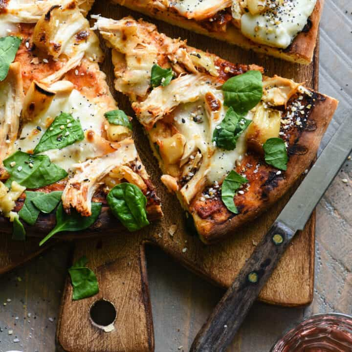 Overhead photo of cut flatbread on cutting board with knife.