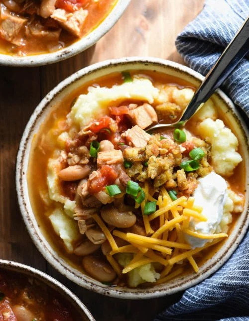 This Leftover Turkey Chili recipe lets you use up almost all of your Thanksgiving leftovers in one bowl! Easy turkey chili is spooned over mashed potatoes and topped with Crunchy Stuffing Bits! | foxeslovelemons.com