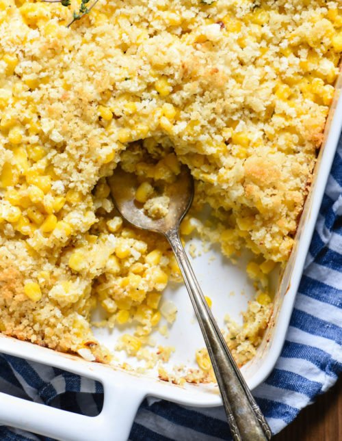 Closeup of casserole dish filled with corn casserole, with some casserole scooped out with spoon. On top of blue and white striped linen.