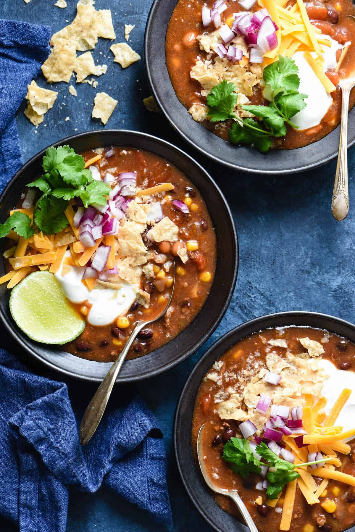 Three black bowls filled with taco soup and garnished with sour cream, lime, cilantro, cheese, red onion and crushed tortilla chips.