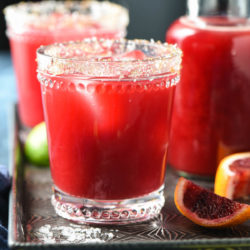 Blood orange margaritas on serving tray with salt garnish.