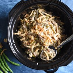 Overhead view of black crockpot insert filled with green bean casserole, on blue background.