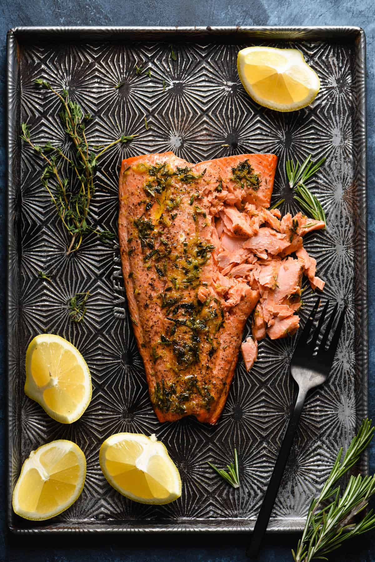 Large fillet of sockeye salmon being flaked with fork on top of star printed baking sheet. Lemon wedges and fresh herbs garnish the scene.