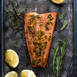 Large fillet of sockeye salmon on top of star printed baking sheet. Lemon wedges and fresh herbs garnish the scene.