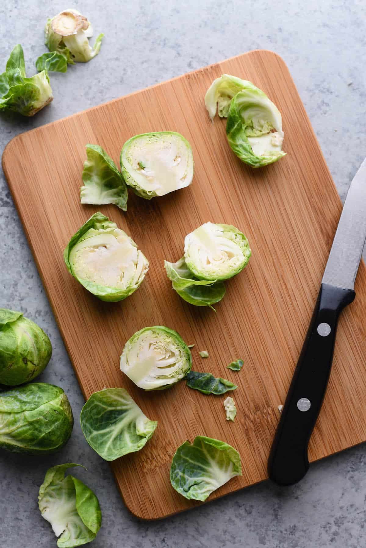 Halved raw brussels sprouts on cutting board with paring knife.