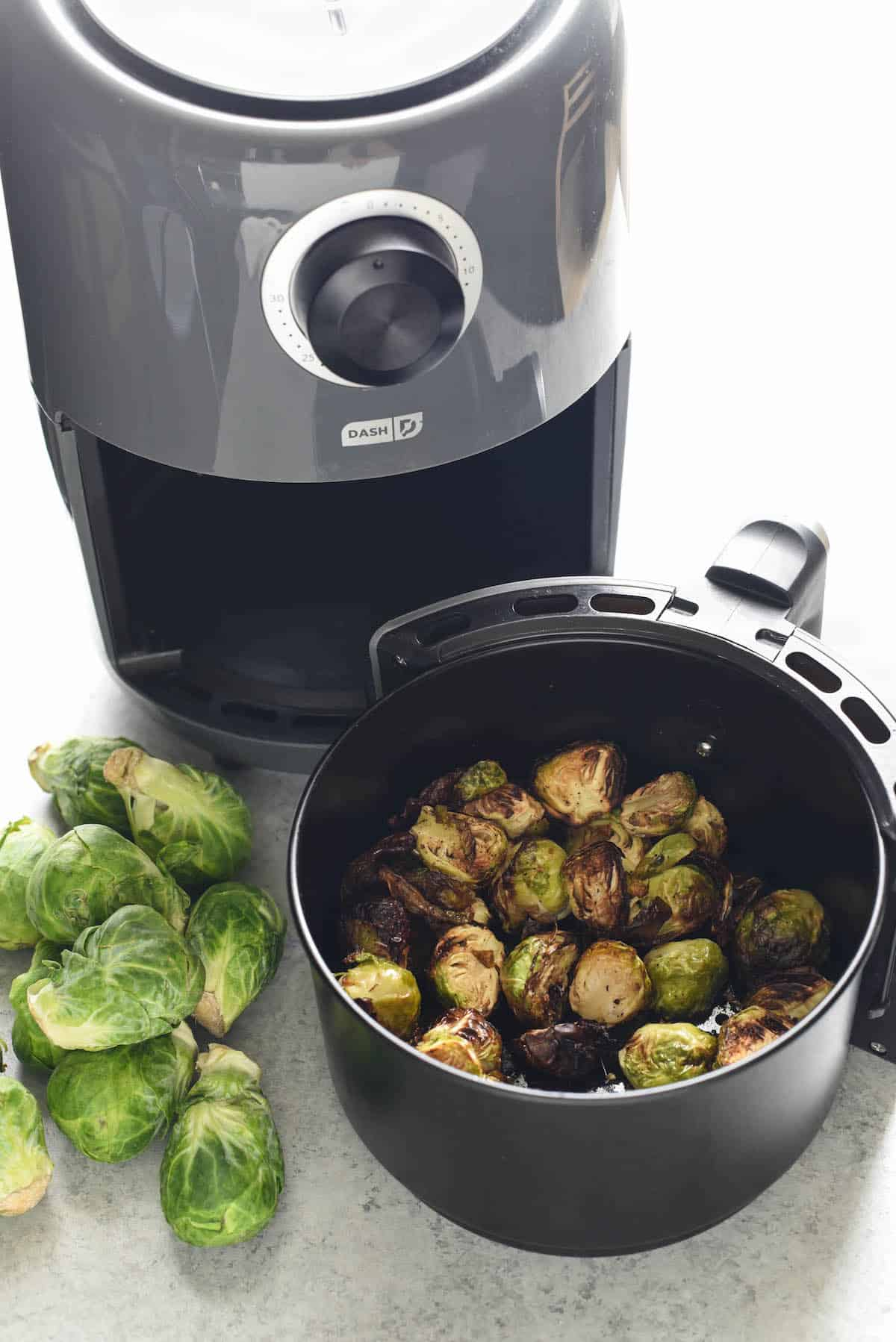 Air fryer basket with air fried brussels sprouts inside, with air fryer in background. Raw brussels sprouts on table.