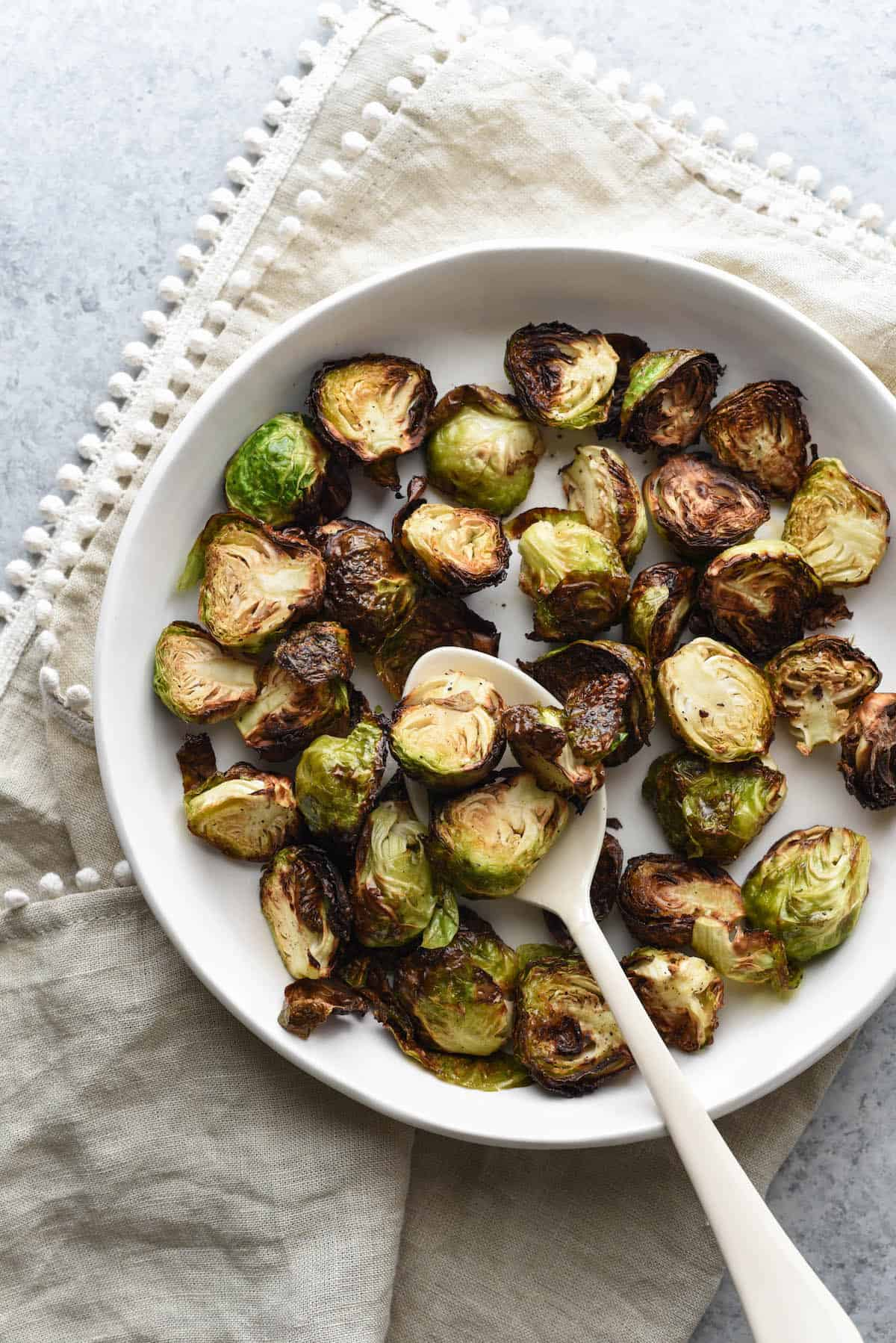Air fried brussels sprouts in shallow white bowl with white serving spoon, on top of beige linen with pom pom edging.