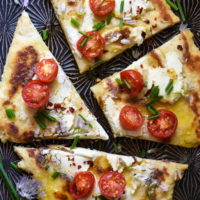 Overhead image of flatbread pizza topped with goat cheese, tomatoes and chives.