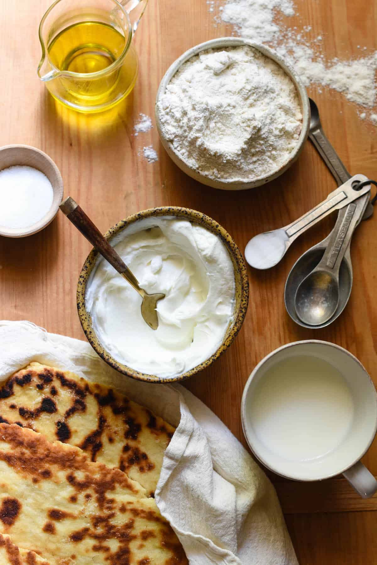 Overhead image of ingredients for homemade flat bread - olive oil, flour, baking soda, yogurt, milk and sugar. Finished flatbreads alongside.