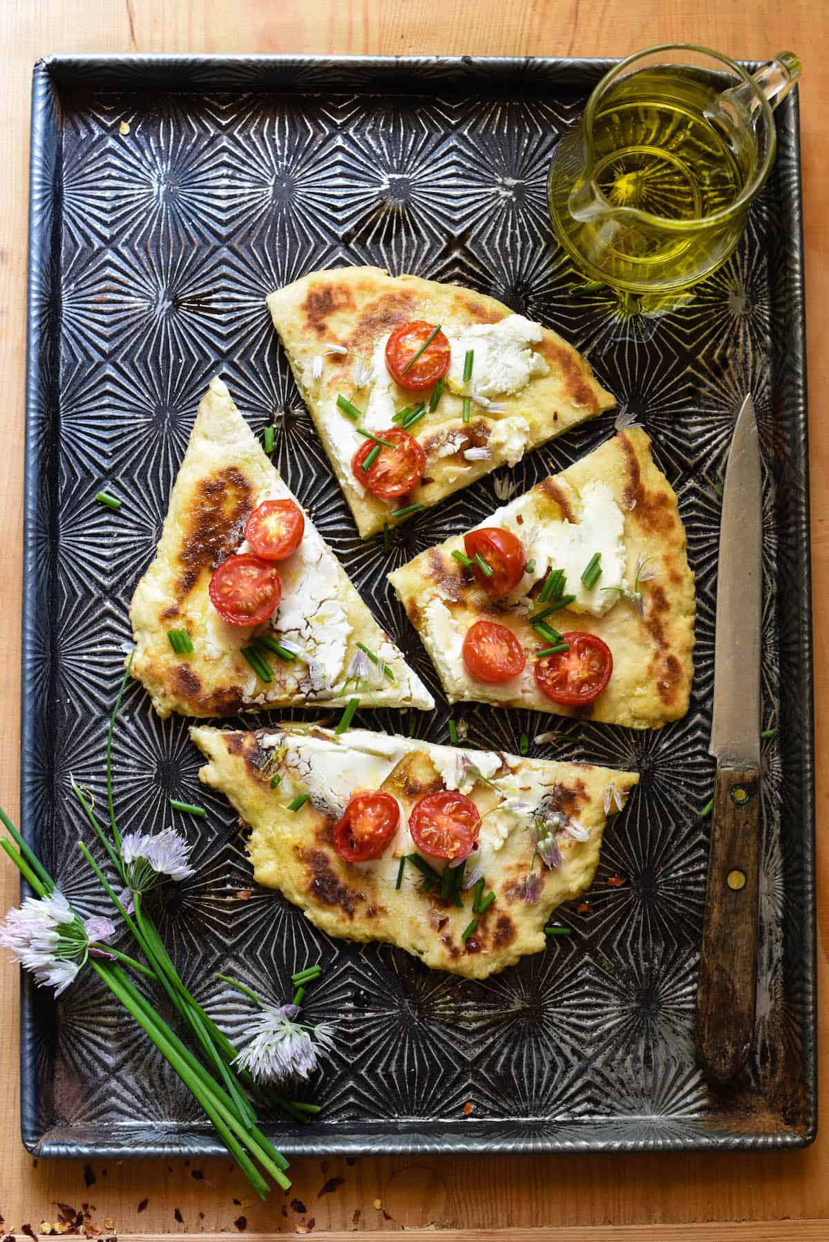 Overhead image of thin crust topped with tomatoes and goat cheese. Chives and chive flowers on pan with flatbread.