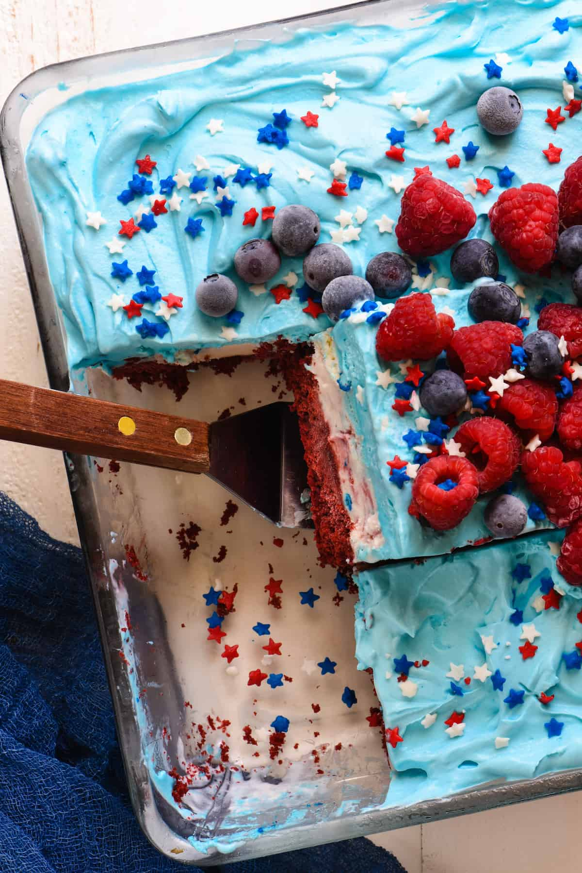 Closeup of pan of red white and blue frozen cake topped with berries. One piece cut and tilted, resting on spatula.